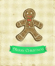 Gingerbread man and green ribbon on patterned background with snowflakes and old paper texture christmas illustration Royalty Free Stock Photo