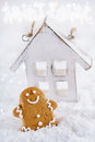 Gingerbread man and wooden house on a festive christmas snow background nice postcard Stock Photo