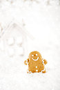 Gingerbread man and wooden house on a festive christmas snow background nice postcard Stock Photos