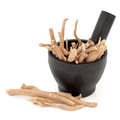 Ginseng herbal medicine in a mortar with pestle over white background Stock Photos