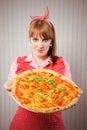 Giovane casalinga che tiene una pizza vegetariana per pranzo Fotografie Stock