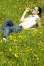 Giovane donna in natura che sente l'odore di un fiore Immagine Stock