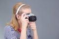 Giovane donna in retro vestiti che posano con la macchina fotografica della foto sopra grey Fotografia Stock Libera da Diritti