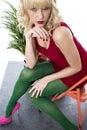 Giovane donna sexy che posa sedia in breve mini dress Fotografia Stock Libera da Diritti