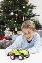 Giovane ragazzo felice che gioca con toy car at home Immagine Stock Libera da Diritti