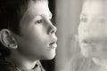 Giovane ragazzo nel pensiero con la riflessione della finestra Fotografia Stock Libera da Diritti