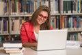 Giovane studente using her laptop in una biblioteca Immagini Stock