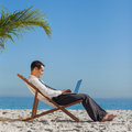 Giovane uomo d affari sulla sua sedia di spiaggia facendo uso del suo computer portatile Fotografia Stock Libera da Diritti