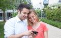 Giovani coppie che cercano le immagini sul telefono Fotografia Stock Libera da Diritti