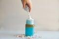 Girl is adding cream in cup of colored blue milk. Milk shake, cocktaill, frappuccino. Unicorn coffee