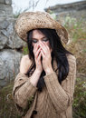 Girl against background of nature and old concrete wall portrait a covering face with hands in a straw hat Stock Photos