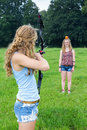 Girl aiming arrow of compound bow at apple on head of woman Royalty Free Stock Photo