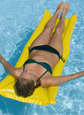 Girl on an airbed in a swimming pool Stock Images