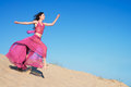 Girl in airy crimson dress running on sand dunes full length portrait of a beautiful Royalty Free Stock Image