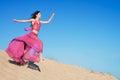 Girl in airy crimson dress running on sand dunes Royalty Free Stock Photo