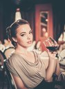 Girl alone in a restaurant beautiful young with glass of red wine Royalty Free Stock Photography