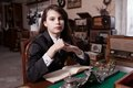 Girl in antique shop thoughtful suit sat at desk Stock Photography