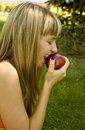 image photo : Girl with an apple on a green lawn
