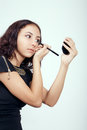 Girl applying makeup young pretty facial cosmetics Stock Images
