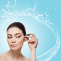 Girl applying serum beautiful young woman anti ageing moisturizing to under eye area isolated over light blue background with Royalty Free Stock Photo