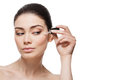 Girl applying serum beautiful young woman anti ageing moisturizing to under eye area isolated over white background copy space Royalty Free Stock Photo