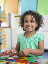 Girl assembling puzzles in classroom portrait of smiling little Stock Photography