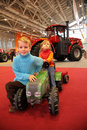 Girl astride small tractor, the boy sits next Royalty Free Stock Photos