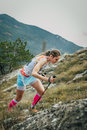 Girl athlete with walking sticks going uphill Royalty Free Stock Photo