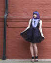Girl with attitude acting sweet image of a sassy blue and purple hair in a short black and purple dress she is standing against a Stock Photography