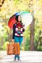 Girl at autumn alley brunette holding suitcase and umbrella in the park Royalty Free Stock Photography