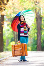 Girl at autumn alley brunette holding suitcase and umbrella in the park Royalty Free Stock Photos