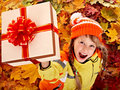 Girl in autumn orange  hat on leaf and gift box. Royalty Free Stock Photo