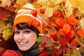 Girl in autumn orange hat, leaf group,  flower. Royalty Free Stock Photo