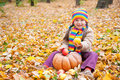 Girl in autumn park with pumpkin and apples at day Royalty Free Stock Photo