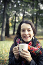 Girl in an autumn part with a white cup of hot drink Royalty Free Stock Photo