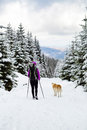 Girl backpacker trekking in winter forest with dog Royalty Free Stock Photo