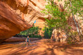 Girl Backpacker walking under Natural Bridge Arch Coyote Gulch Royalty Free Stock Photo