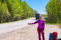 Girl with backpacks hitchhike a car on the road in purple Stock Photos