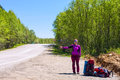 Girl with backpacks hitchhike a car on the road in purple Stock Photo