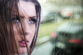 Girl bad weather cute by rainy window in Royalty Free Stock Image