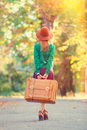 Girl with bag redhead in hat and in the autumn park Royalty Free Stock Photo
