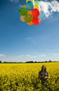 Girl with balloons on canola field. Royalty Free Stock Images