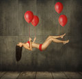 Girl and balloons a is flying on red the tied to her hands feet Royalty Free Stock Photo