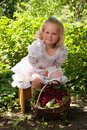 Girl with basket of cherries eating in the garden Royalty Free Stock Photos