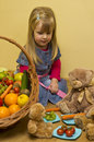 Girl with basket of fruit and vegetables a cute young a large playing teddy bear toys Royalty Free Stock Photography