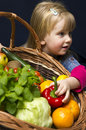 Girl with basket of ripe fruit and vegetables black studio background Royalty Free Stock Photo