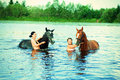 Girl bathe horse in a river young Stock Images