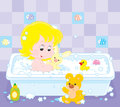 Girl bathing little playing with toys in a bath with foam Stock Photo