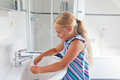 Girl in bathroom little washing her toothbrush inside the Royalty Free Stock Image
