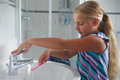 Girl in bathroom little washing her toothbrush inside the Royalty Free Stock Photo